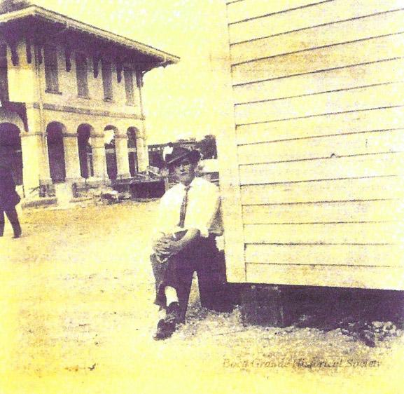Black White Photo of Man sitting next to building
