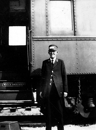conductor standing next to train