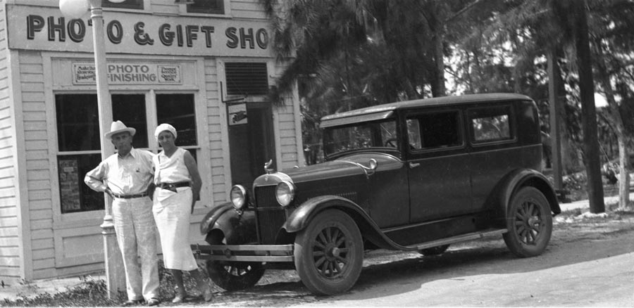 historical photo: Couple standing next to old car