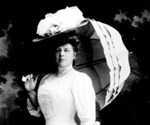 black and white photo of woman in white dress, wearing hat and sun umbrella