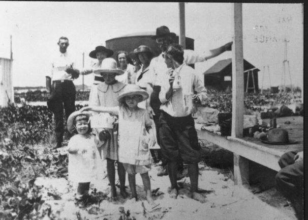 black and white family photo with water and factory in background